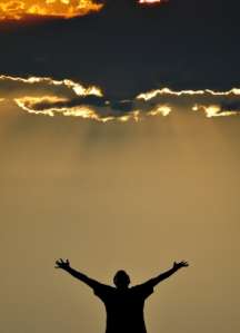 Silhouette of a man standing under a sunset sky with arms outstretched.