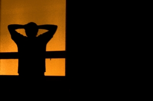 Silhouette of a person standing with ther arms behind their head